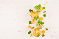 Freshly blended orange kumquat and green kiwi fruit smoothie in glass jars with straw, mint leaf, cut ripe berry, top view. Stock Photo