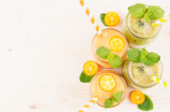 Freshly blended orange kumquat and green kiwi fruit smoothie in glass jars with straw, mint leaf, cut ripe berry, top view. Stock Image