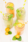 Freshly blended orange kumquat and green kiwi fruit smoothie in glass jars with straw, mint leaf, cut ripe berry. White wooden board background, vertical Stock Photos