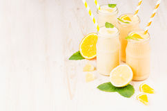 Freshly blended orange and yellow lemon smoothie in glass jars with straw, mint leaf, copy space. White wooden board background. Freshly blended orange and Royalty Free Stock Photo