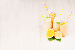 Freshly blended orange and yellow lemon smoothie in glass jars with straw, mint leaf, copy space. White wooden board background Stock Image