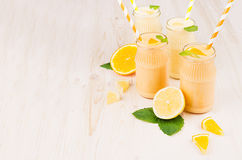 Freshly blended orange and yellow lemon smoothie in glass jars with straw, mint leaf, copy space. White wooden board background Royalty Free Stock Photo
