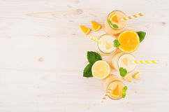 Freshly blended orange and yellow lemon smoothie in glass jars with straw, mint leaf, slices orange and lemon, top view. Stock Photography