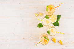 Freshly blended orange and yellow lemon smoothie in glass jars with straw, mint leaf, slices orange and lemon, top view. Royalty Free Stock Photos