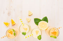 Freshly blended orange and yellow lemon smoothie in glass jars with straw, mint leaf, slices orange and lemon, top view. Freshly blended orange and yellow lemon Stock Images