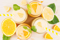 Freshly blended orange and yellow lemon smoothie in glass jars with straw, mint leaf, top view, close up. White wooden board background Royalty Free Stock Photography