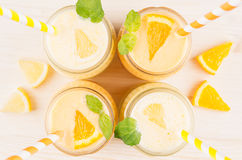Freshly blended orange and yellow lemon smoothie in glass jars with straw, mint leaf, top view, close up. Royalty Free Stock Photography