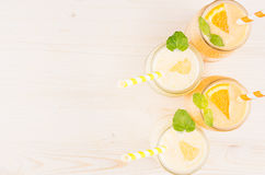 Freshly blended orange and yellow lemon smoothie in glass jars with straw, mint leaf, top view. White wooden board background, cop. Y space Stock Photography