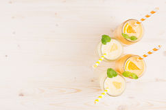 Freshly blended orange and yellow lemon smoothie in glass jars with straw, mint leaf, top view. White wooden board background, copy space Royalty Free Stock Photo