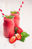 Freshly blended red strawberry fruit smoothie in glass jars with straw, mint leaf, cut ripe berry. White wooden board background,. Freshly blended red strawberry Royalty Free Stock Photography