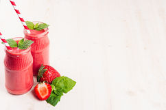 Freshly blended red strawberry fruit smoothie in glass jars with straw, mint leaf, cut ripe berry. White wooden board background,. Freshly blended red strawberry Stock Photography