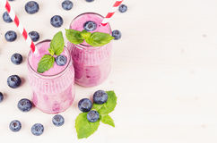 Freshly blended violet blueberry fruit smoothie in glass jars with straw, mint leaves, berries. White wooden board background, cop Royalty Free Stock Photo