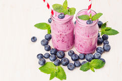 Freshly blended violet blueberry fruit smoothie in glass jars with straw, mint leaves, berries. White wooden board background, cop Stock Photography