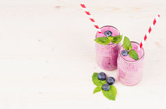 Freshly blended violet blueberry fruit smoothie in glass jars with straw, mint leaves, berries. White wooden board background, copy space Stock Photography