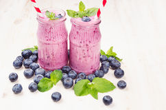 Freshly blended violet blueberry fruit smoothie in glass jars with straw, mint leaves, berries. White wooden board background, copy space Stock Photo