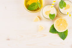 Freshly blended yellow lemon smoothie in glass jars with straw, mint leaf, cut lemon, honey, top view. White wooden board background, copy space Stock Photo