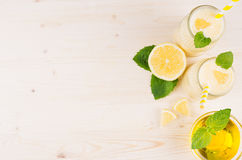 Freshly blended yellow lemon smoothie in glass jars with straw, mint leaf, cut lemon, honey, top view. White wooden board background, copy space Royalty Free Stock Photography
