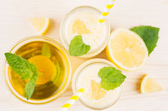 Freshly blended yellow lemon smoothie in glass jars with straw, mint leaf, cut lemon, top view, close up. Freshly blended yellow lemon smoothie in glass jars Royalty Free Stock Image