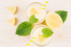 Freshly blended yellow lemon smoothie in glass jars with straw, mint leaf, cut lemon, top view, close up. Freshly blended yellow lemon smoothie in glass jars Stock Photos