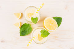 Freshly blended yellow lemon smoothie in glass jars with straw, mint leaf, cut lemon, top view, close up. Freshly blended yellow lemon smoothie in glass jars Royalty Free Stock Photos