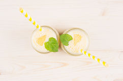 Freshly blended yellow lemon smoothie in glass jars with straw, mint leaf, top view. White wooden board background, copy space Stock Image