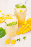Freshly blended yellow mango fruit smoothie in glass jars with straw, mint leaves, mango slices, close up. Soft white wooden board. Freshly blended yellow mango Royalty Free Stock Photo