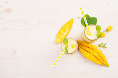 Freshly blended yellow mango fruit smoothie in glass jars with straw, mint leaves, mango slices, top view. White wooden board background, copy space Royalty Free Stock Photography