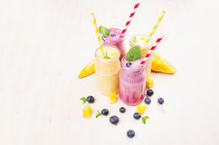 Freshly blended yellow and violet  fruit smoothie in glass jars with straw, mint leaves, mango slices, berry. Freshly blended yellow and violet fruit smoothie Royalty Free Stock Images