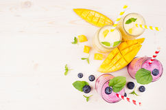 Freshly blended yellow and violet  fruit smoothie in glass jars with straw, mint leaves, mango slices and berry, top view. Soft white wooden board background Stock Image