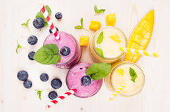 Freshly blended yellow and violet fruit smoothie in glass jars with straw, mint leaves, mango slices, berry, top view. Freshly blended yellow and violet  fruit Stock Photography