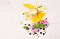 Freshly blended yellow and violet fruit smoothie in glass jars with straw, mint leaves, mango slices and berry, top view. Freshly blended yellow and violet Stock Image