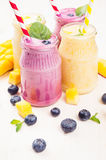 Freshly blended yellow and violet  fruit smoothie in glass jars with straw, mint leaves, mango slices, blueberry, close up. Soft w. Freshly blended yellow and Stock Image