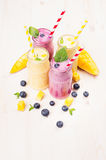 Freshly blended yellow and violet  fruit smoothie in glass jars with straw, mint leaves, mango slices, blueberry. Soft white wooden board background Royalty Free Stock Image