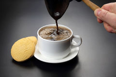 Freshly brewed black coffee from the turks poured in a white Cup Royalty Free Stock Images