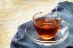 Freshly brewed black tea in a glass cup, steaming hot drink on a stock image