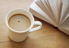 Freshly brewed coffee cup. Freshly brewed coffee cup against book Royalty Free Stock Image