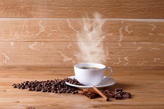 Freshly brewed coffee. Coffee cup and saucer on a wooden table. Oak background Royalty Free Stock Photos