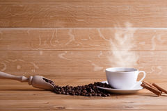 Freshly brewed coffee. Coffee cup and saucer on a wooden table. Oak background Royalty Free Stock Images