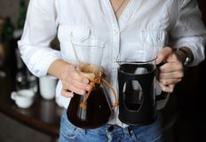 Freshly brewed coffee in glass jars in the hands of barista girl in a white shirt close-up. Freshly brewed coffee in glass jars in the hands of a barista girl in Stock Image