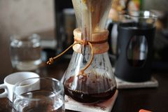 Freshly brewed coffee in a glass jug on the background of coffee accessories Stock Photography