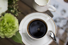 Freshly brewed coffee. Overhead view of strong black freshly brewed coffee in a cup and saucer with spoon and a small milk jug to the side, with copyspace Stock Photos