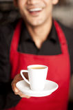 Freshly brewed coffee served with a smile. Cheerful shop owner serving freshly brewed coffee to you Stock Photography