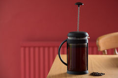 Freshly brewed coffee on table in red room in a cafetiere. Freshly brewing cafetiere on a kitchen table in a red kitchen with some coffee beans in front of it Stock Photos