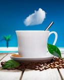 Freshly brewed coffee at a tropical resort. Freshly brewed cup of aromatic coffee with fresh coffee beans on a wooden deck overlooking the ocean at a tropical Stock Photography