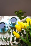 Freshly brewed coffee. Two blue cup of coffee with yellow tulips on an old table Stock Photos