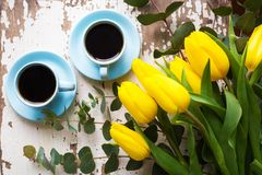Freshly brewed coffee. Two blue cup of coffee with yellow tulips on an old table Royalty Free Stock Photos