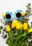 Freshly brewed coffee. Two blue cup of coffee with yellow tulips on an old table, top view Royalty Free Stock Images