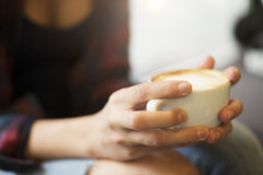 Freshly brewed cup of coffee held by girls hands. Close up shot of girls hands holding a cup of coffee Stock Images