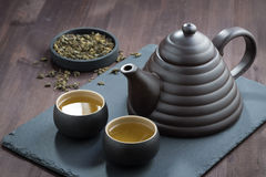 Freshly brewed green tea in ceramic ware on wooden table Stock Photography
