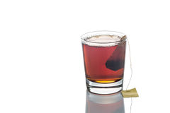 Freshly brewed hot tea with teabag in transparent glass. Freshly brewed organic hot black tea with teabag in transparent glass isolated in white Stock Photos